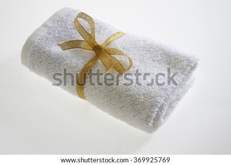 White towel with golden ribbon  - stock photo