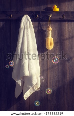 White towel with loofah hanging on wall with floating bubbles and sunlight filtering through - vintage tone effect - stock photo