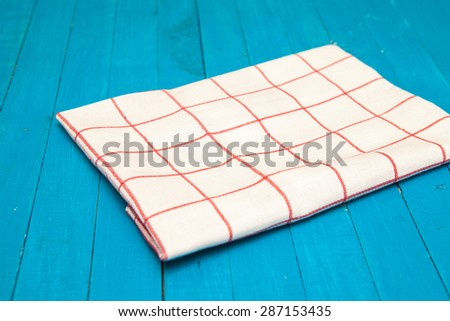 white towel with red stripes on a blue wooden background