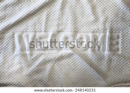 White towel with wording welcome for hotel customers - stock photo