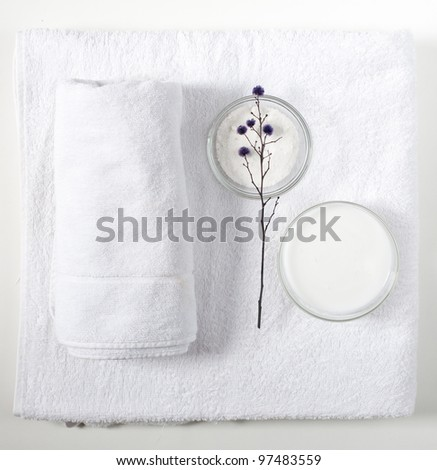 White towels, bath salt and body cream on a white background - stock photo
