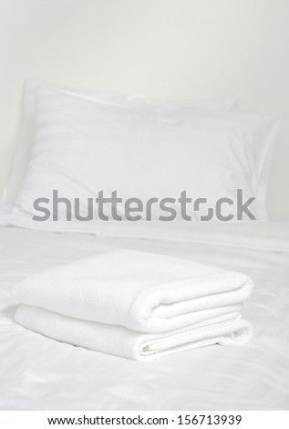 white towels lying on bed with pillows