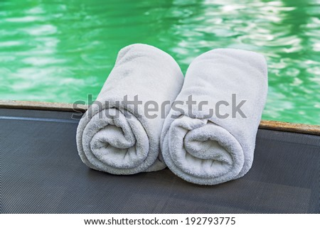 White towels on pool chairs at swimming pool  - stock photo