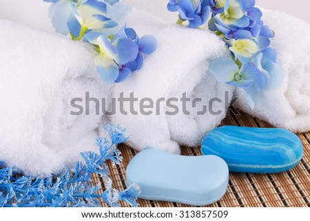 White towels with blue flowers and soaps closeup picture. - stock photo