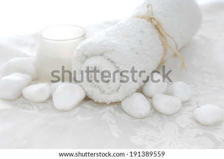 White towels with white stones and candle on lace - stock photo