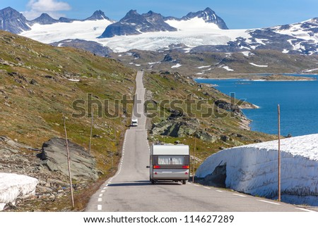white trailer on mountain road near glacier and lake - stock photo