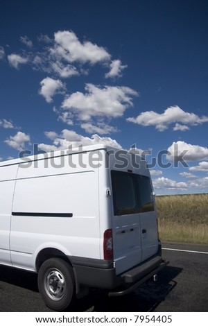 White transit van against a blue sky background - stock photo