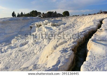 White travertine terraces made from the hots springs leaving deposits of calcium  at Pamukkale or Cotton Castle next to  Hierapolis, Turkey in the evening - stock photo