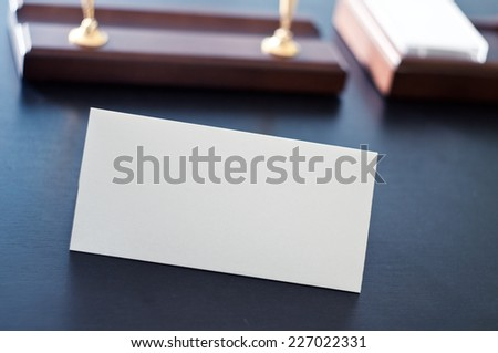White triangular sign for the label standing on a table. Room for you text. - stock photo