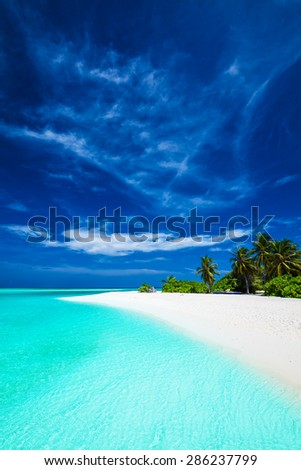 White tropical beach with beautiful sky with few palm trees and blue lagoon - stock photo
