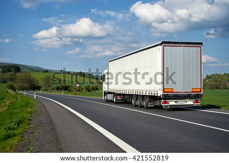 White truck departing on an asphalt road meander trough the green fields. Warning traffic sign Bend to right. Wooded mountains in the background. Sunny spring day with blue skies and white clouds. - stock photo