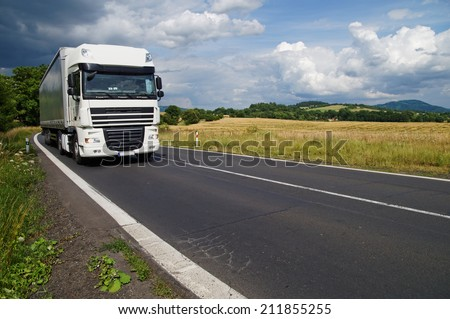 White truck on the road in a rural landscape, in the background of a green cornfield and wooded mountains - stock photo