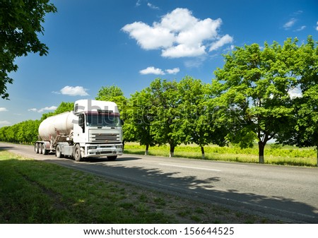 white truck with tank on summer road - stock photo