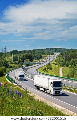 White trucks drive along an asphalt highway with electronic toll gate in a wooded landscape. View from above. Sunny summer day with blue skies and white clouds. - stock photo