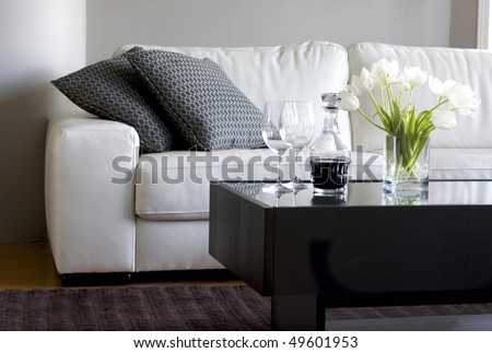 white tulips and red wine in modern living room - stock photo
