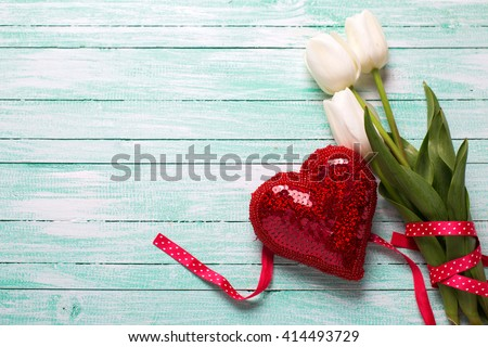 White tulips flowers and decorative red heart on turquoise wooden background. Selective focus. Place for text. - stock photo