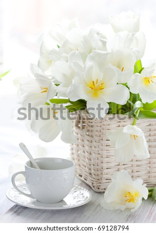 white tulips in a basket and cup of tea on the wooden table - stock photo
