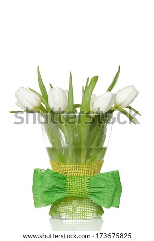 White tulips in glass vase with big green bow. - stock photo
