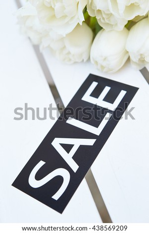 White tulips with sale tag - stock photo