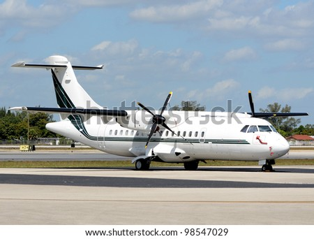 White turboprop airplane parked on a tarmac - stock photo
