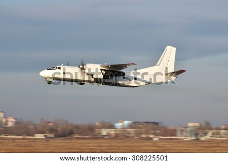 White turboprop cargo plane takes off on sunset with cloudy sky on the background