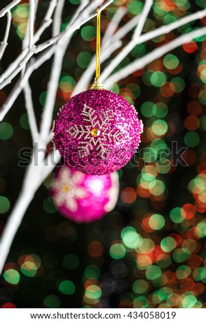 White twigs with Christmas tree baubles in front of a green red background