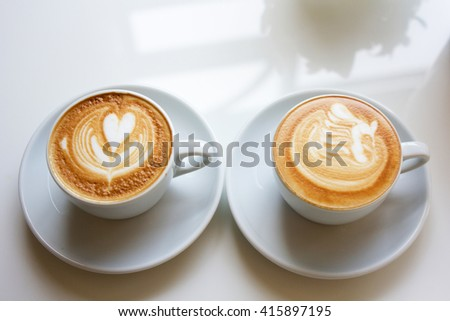 white two cups of Cappuccino coffee with froth heart and bird shaped - stock photo