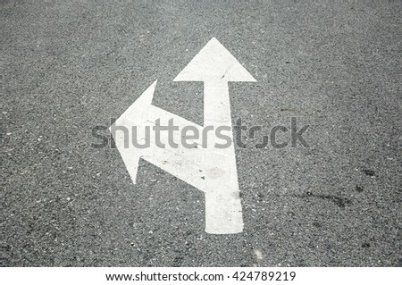white two way arrow symbol on a black asphalt road surface - stock photo