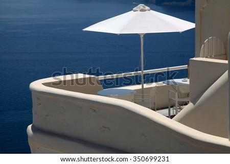 White umbrella on greek balcony resort house and Aegean sea in Oia, Santorini island, Greece - stock photo