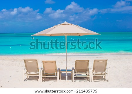 White umbrellas and sunbeds at tropical beach - stock photo