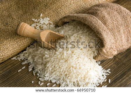 White uncooked rice in small burlap sack - stock photo