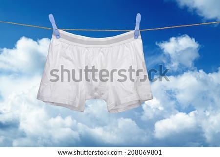 white underwear on a string against cloudy blue sky - stock photo