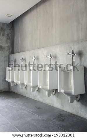 White urinals in men's bathroom - stock photo