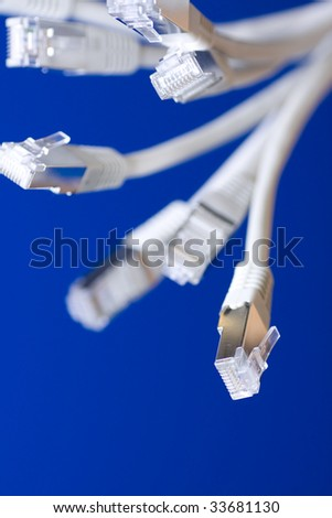 white utp cat5 network cables blue background - stock photo