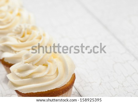 White vanilla cupcakes in a row. focus is on front cupcake. - stock photo