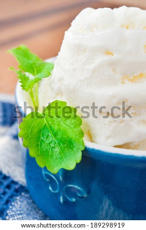 White vanilla ice-cream with mint leaf in blue porcelain bowl. Indoors still life. Closeup.