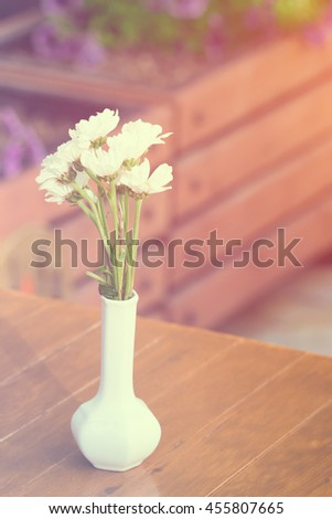 White vase with flowers on a wooden table - stock photo