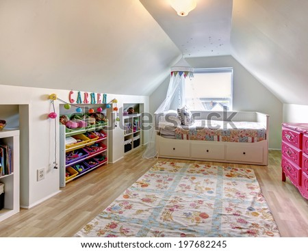 White vaulted ceiling kids room with hardwood floor and rug. Room furnished with single bed, pink antique dresser and  storage units for toys - stock photo