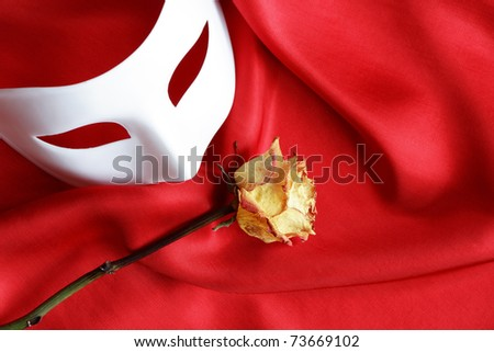 White venetian mask and dry yellow rose on red cloth background - stock photo
