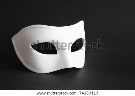 White venetian mask lying on black background