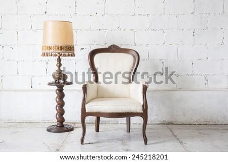 White vintage armchair on white wall. - stock photo