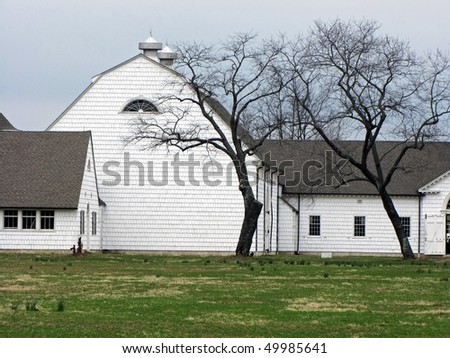 White vintage barn complex with grass and trees.