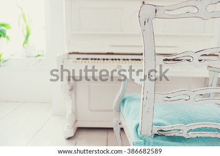 White vintage chair and piano in a white room - stock photo