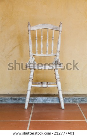 white Vintage chair near yellow old wall - stock photo
