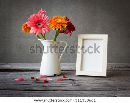 White vintage photo frame and flowers on wooden table over grunge background - stock photo