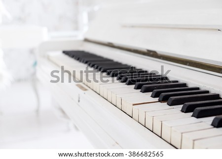 White vintage piano in a white room - stock photo