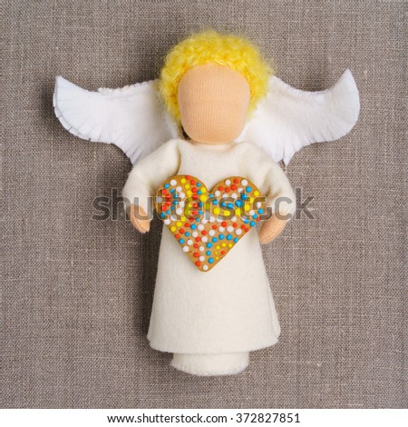 White waldorf doll angel, holding gingerbread heart, lying on a gray linen fabric background - stock photo