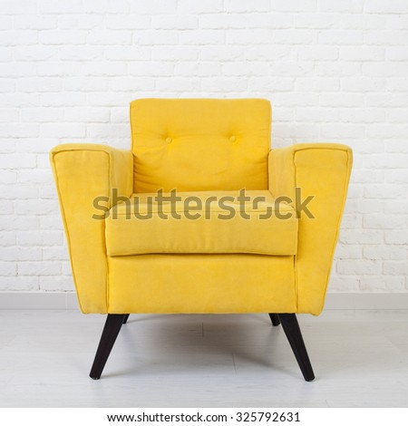White wall texture with a retro yellow armchair - stock photo