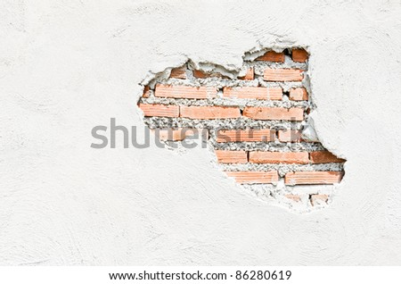 White wall which cracked until see the orange brick inside. - stock photo