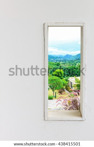 White wall window with home in mountain view, vertical landscape concept background.